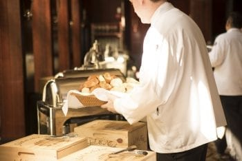 waiter serving bread and food into the counter