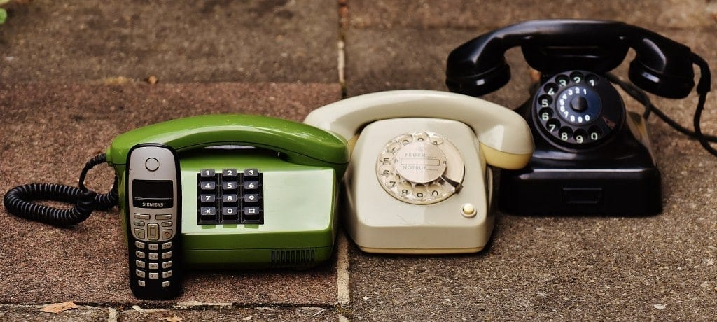 Vintage telephones listed on the concrete floor